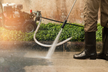 High pressure deep cleaning..Worker cleaning driveway with gasoline high pressure washer ,professional cleaning services.