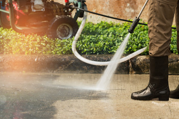High pressure deep cleaning. .Worker cleaning driveway with gasoline high pressure washer ,professional cleaning services.