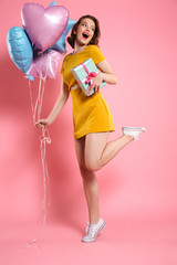 Cheerful young lady in yellow dress holding ballons with gift