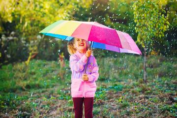 Счастливая девочка в розовом свитере играет в парке с красивым радужным зонтом. Девочка с разноцветными зонтом под дождем.