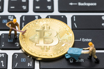 Miniature man are digging Mining Golden bitcoins on thai keyboard or laptop. using as background business concept.