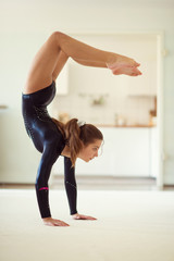 Young pretty girl has training gymnastics at home in white interior