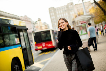 Young woman waiting for taxi or bus on the street in the city