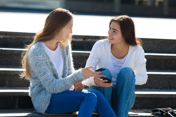 Two Happy Female Teenagers Talking Together in the Street