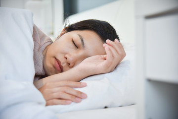 Asian woman sleeping on her bed.