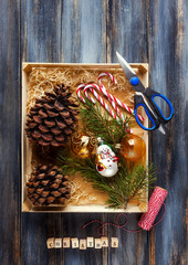 preparing for winter holidays, gift wrapping, box with Christmas decoration and gifts , pine cones . on a wooden background