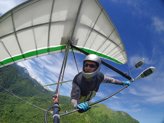 Hang glider pilot soaring the thermal updrafts above green mountain hills