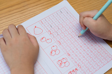 kid learns to write Arabic numerals by following guides