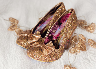 A brides beautiful, golden, glittery, sexy pair of individual stylish wedding shoes, on a white creamy material surface.