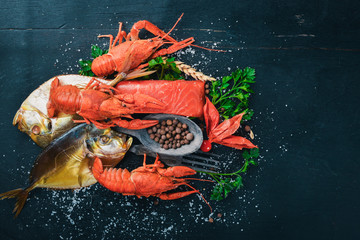 Seafood. Fish Vomer, lobster, salmon. On a wooden background. Top view. Free space for text.