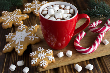 Foto auf Acrylglas Schokolade Hot chocolate with marshmallows in the red cup and Christmas cookies on the wooden cutting board