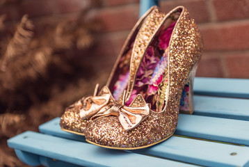 A brides beautiful, golden, glittery, unique, sexy pair of individual stylish wedding shoes, on a blue wooden surface outdoors.