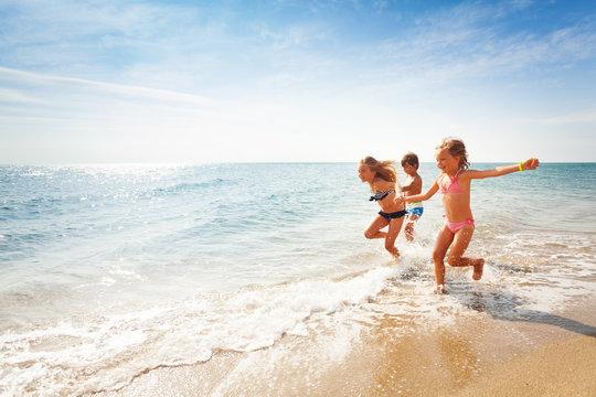 Happy friends running along edge of sea in summer