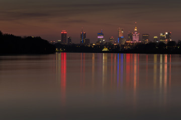 Colorful nocturnal skyline of Warsaw skyscrapers and their reflection in the Vistula River