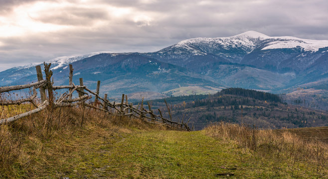 wooden fence on hills of mountainous countryside. agricultural fields in late autumn gloomy weather. mountain ridge with snowy tops in the distance