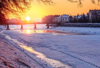 winter sunrise on the bank of ice covered river Uz. Sun over the bridge of old European town Uzhgorod