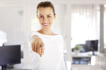Hey you. Close-up portrait of a smiling young woman raising her hand and pointing at you with her finger while standing at office.