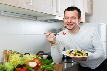Happy  handsome man holding plate with salad