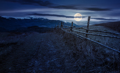 wooden fence in mountainous countryside at night in full moon light. mountain ridge with snowy tops in the distance