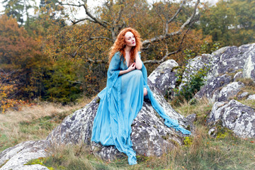 Beautiful woman with long curly red hair wearing  long teal dress  sitting on rock