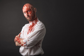 white bold bearded Caucasian male model guy man attractive wearing white shirt and black pants with red face paint makeup