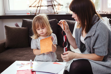 Mother and daughter making a Christmas garland with red and gold glitter paper. Lifestyle image, shallow depth of field.
