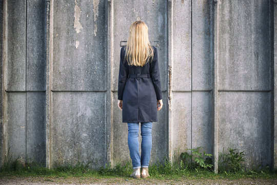 Beautiful lonely blonde woman standing back against city cement wall.