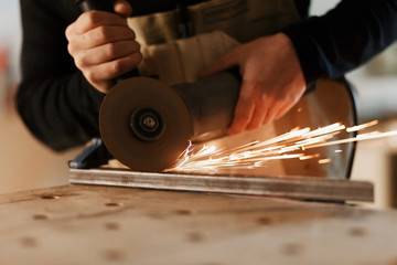 Industrial worker cutting metal with many sharp sparks. Selection focus to cutting machine. Copyspace