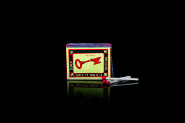 A vintage match box with swastikas and a key  on the front. Isolated studio shot on black background.