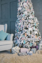 Living room interior with Christmas tree and chair.  Vertical composition photo