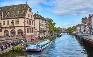 Tourist Boat on river in beautiful downtown of Strasbourg / Housing and river in city of Strasbourg in Alsace France