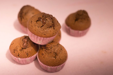 Chocolate muffins still life composition on pink background.