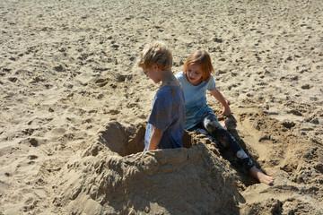 Zwei Kinder spielen im Sand am Strand