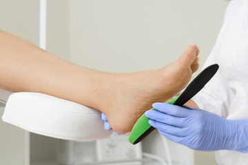 Orthopedic insoles. Fitting orthotic insoles. Flatfoot treatment. Podiatry clinic.