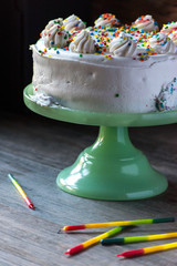birthday cake with white frosting and rainbow cake and candles