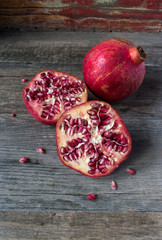 pomegranate slices and whole in rustic setting