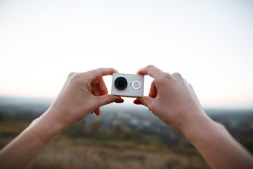Man holds an action camera on the sunset background