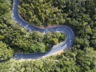Aerial shot looking straight down of a winding two lane road through bush land.