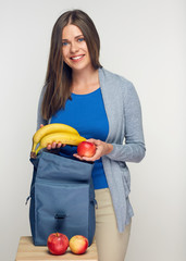 Young woman puts fruit in bag for food.