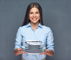 Smiling woman holding stack of plate with kife and fork