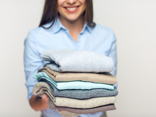 Woman holding stack of folded clothes.