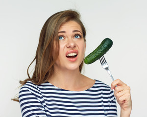 Isolated portrait of woman holding cucumber on fork.