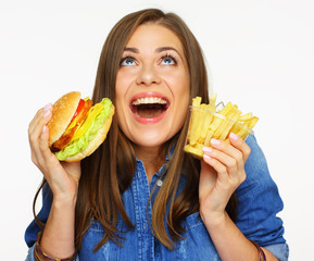 Happy girl holding teasty burger with french fries, looking up.