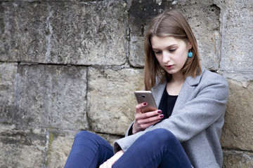 Social Media addiction. young beautiful woman holding a smartphone (psychological problems, media mania)
