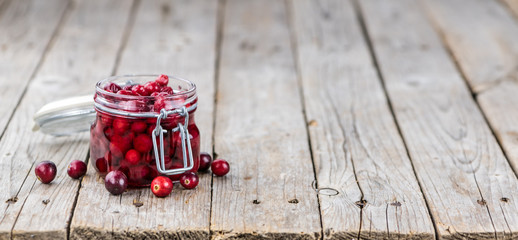 Wooden table with Cranberries (preserved) (detailed close-up shot; selective focus)