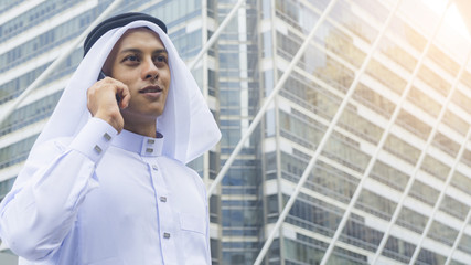 Arab man stands and uses mobile phone at outdoor city space at morning day