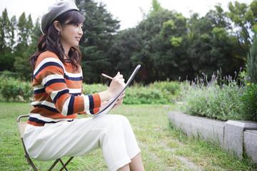 公園で絵を描く女性