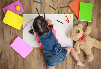 Adorable little girl drawing artwork. Studio shot top view of child on floor