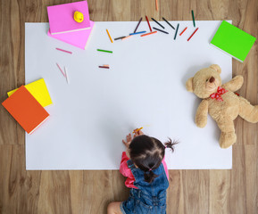 Little Asian girl drawing in paper on floor indoors, top view of child on floor with copy space
