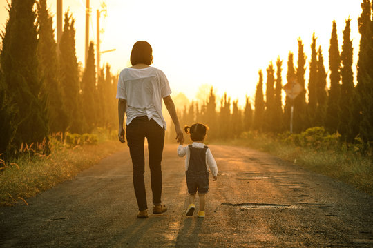 Happy family in the park evening light. The lights of a sun. Mom and baby happy walk at sunset. The concept of a